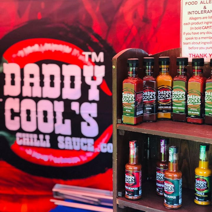 Selection of sauces by Daddy Cool's Chilli Sauce set up at a stall.
