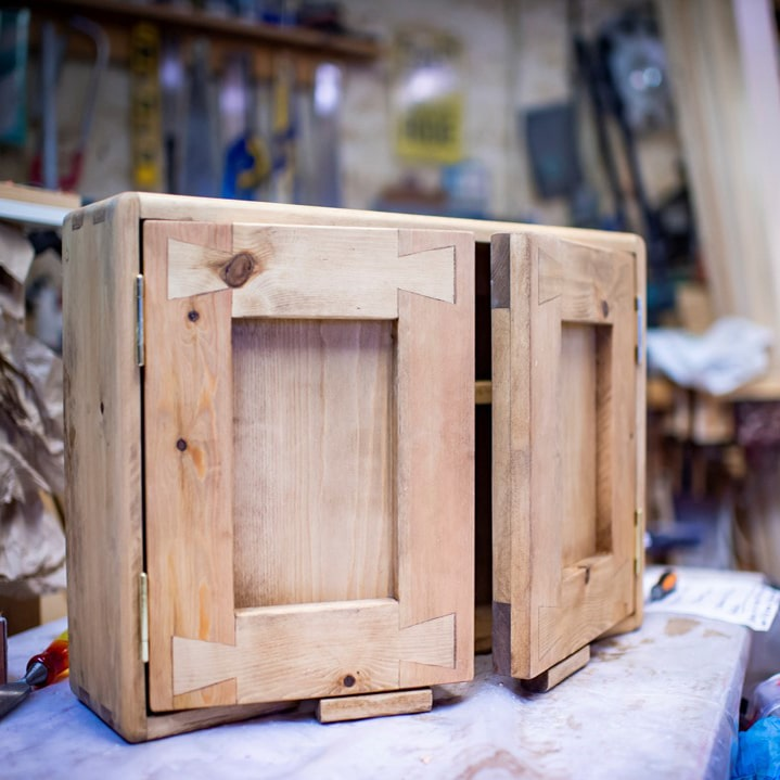 A small two door wood door cabinet which has been handcrafted by Marc Wood Bespoke Joinery.